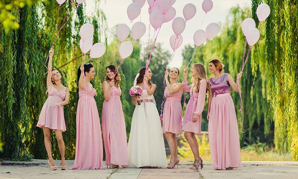 Photo of bride and bridesmaids holding colorful balloons