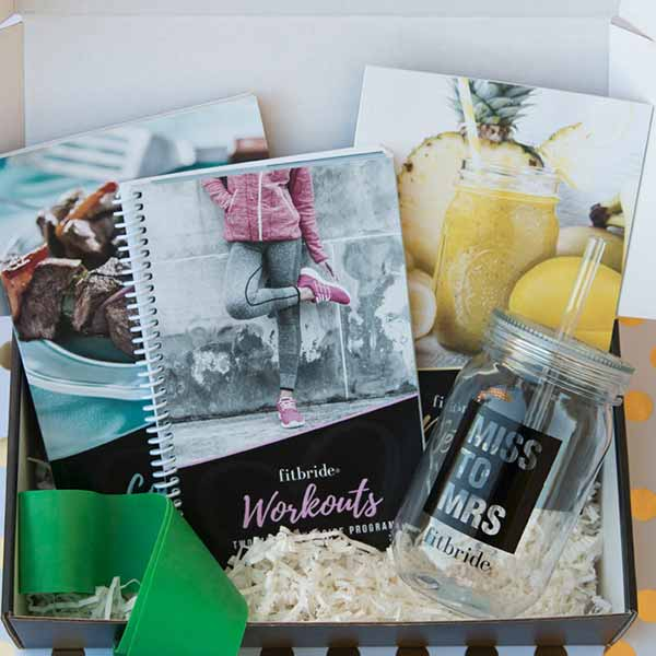 Fitbride box open showing workout book, cookbook, detox guide, mason jar and resistance band