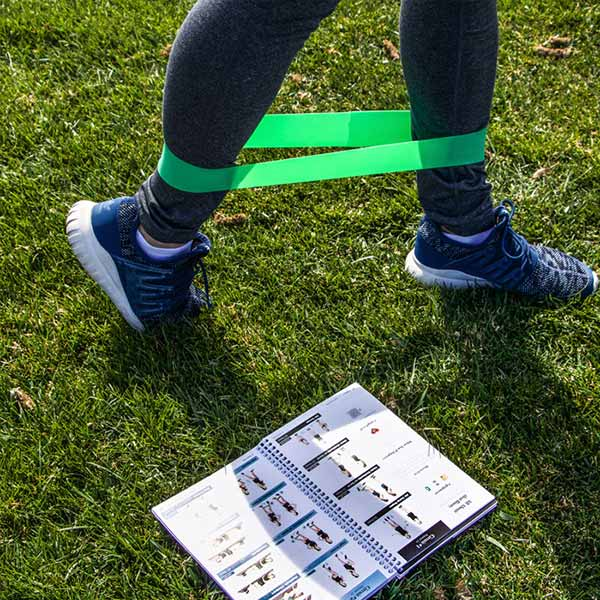 Woman exercising with green resistance band, using the Fitbride workout book